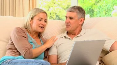 Couple relaxing with laptop on sofa — Stock Video