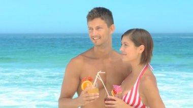Couple posing with cocktails on a beach — Stock Video