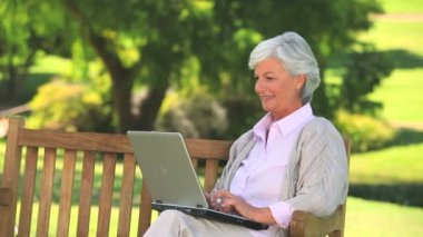 Mature woman surfing on her laptop outdoors — Stock Video