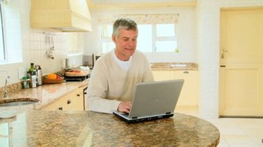 Mature man using a laptop in the kitchen — Stock Video