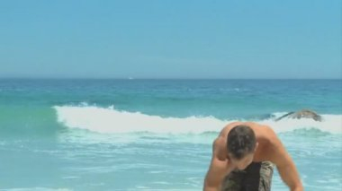 Man coming out of the sea to pick up a soccer ball — Stock Video