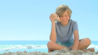 Young smiling boy listening to a shell — Stock Video