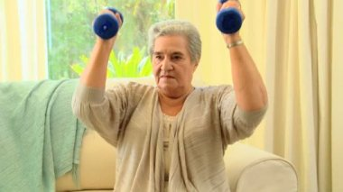Mature woman exercising using dumbbells — Stock Video