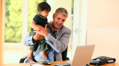 Businessman working at the desk while holding his son in his arms — Stock Video