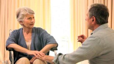 Mujer en silla de ruedas charlando con esposo — Vídeo de Stock