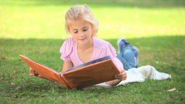 Young girl reading a book outside — Stock Video
