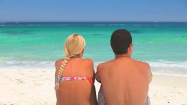 Young man sitting on a beach with his arm around his girlfriend — Stock Video