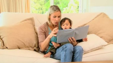 Young mother and baby looking at picture book — Stock Video