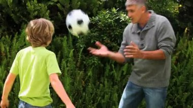 Father and son playing with football in garden — Stock Video
