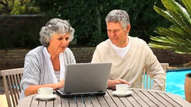 Mature couple working on a laptop in the garden — Stock Video