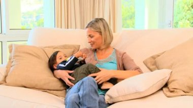 Blonde haired woman bottle-feeding her child — Stock Video
