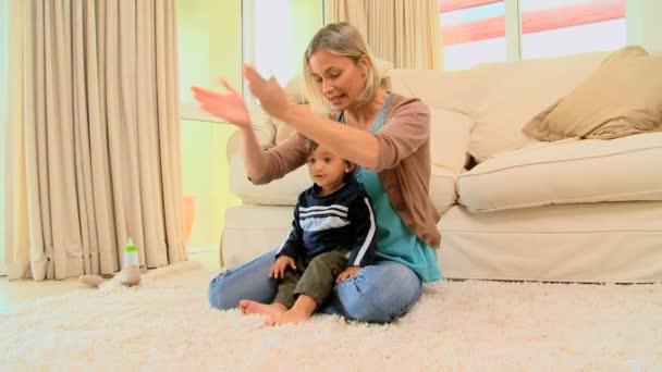 Joven madre jugando con su bebé en la alfombra — Vídeo de stock