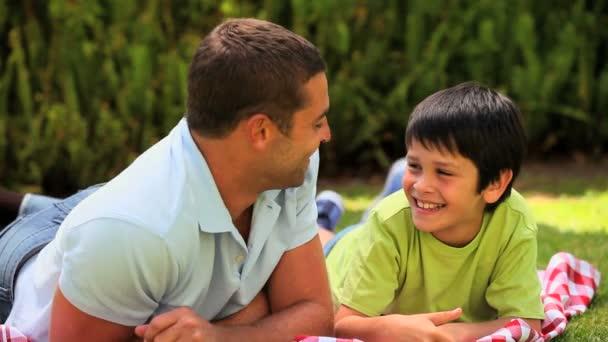 Padre e hijo hablando mentira al aire libre — Vídeo de stock