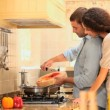 Young woman watching her boyfriend do the cooking — Stock Video #23500055