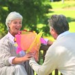 Mature man offering a bunch of flowers to his wife — Stock Video