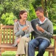Young couple eating  icecream on a park bench — Stock Video