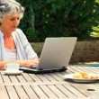 Mature woman working on her laptop outdoors — Stock Video #23500629