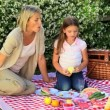 Young woman and her daughter eating fruits in the garden — Stock Video #23500869
