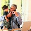 Man in suit minding baby and trying to do office work — Stock Video
