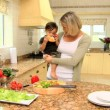 Baby helping mother in the kitchen — Stock Video #23501629