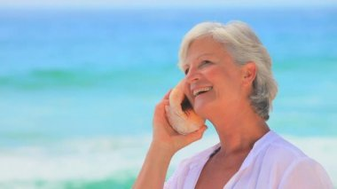 Elderly woman listening to a shell and smiling — Stock Video