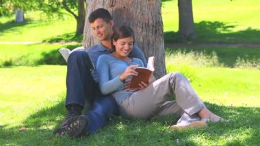 Young couple reading book outdoors — Stock Video