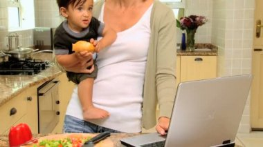 Tired young mother in kitchen trying to work on laptop holding baby — Stock Video