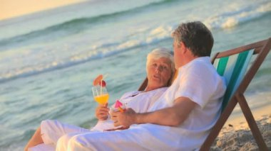 Mature couple drinking cocktails in deckchairs — Stock Video