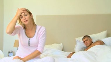 Young woman on bed with headache while husband sleeps — Stock Video
