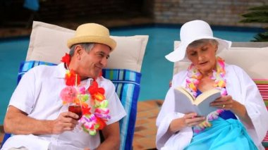 Mature couple with garlands chatting in deckchairs — Stock Video