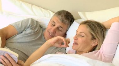Couple in bed sharing a book and laughing — Stock Video