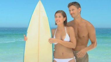 сладкая парочка, смеясь удерживая доску для серфинга — Стоковое видео