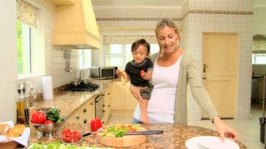 Woman with son in her armsin kitchen — Stock Video