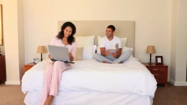 Young couple sitting on their bed sharing a laugh — Stock Video