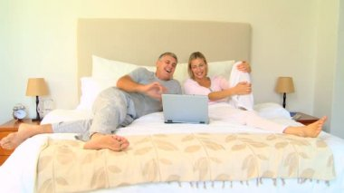 Couple on bed enjoying something hilarious on laptop — Стоковое видео