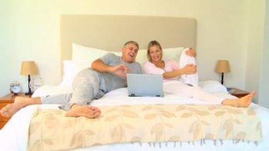 Para na łóżku cieszyć coś zabawne na laptopie — Wideo stockowe