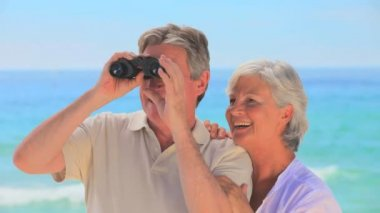 Elderly couple using binoculars — Stock Video