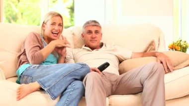 Couple watching hilarious programme on TV — Wideo stockowe
