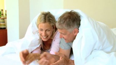 Young couple chatting and laughing under the duvet — Stock Video