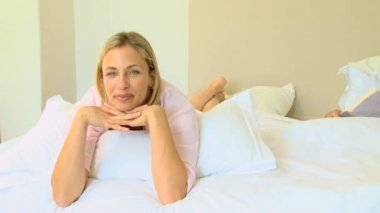 Blonde woman lying on bed looking at the camera — Stock Video