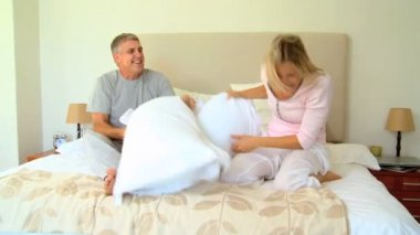 Young couple having pillow fight on bed — Stock Video