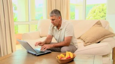 Mature man getting good news on his laptop — Stock Video