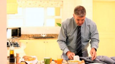 Man in kitchen receiving a call while rushing with breakfast — Vídeo de stock