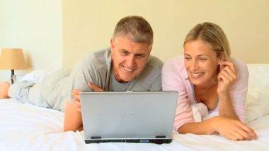 Couple couché regardant un ordinateur portable — Vidéo
