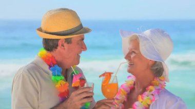Mature couple wearing garlands drinking fruit cocktails — Stock Video