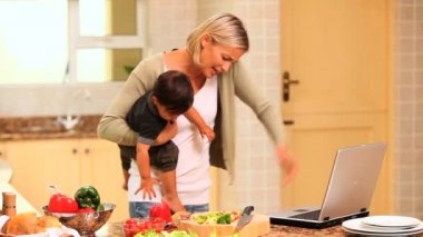 Busy woman phoning and dealing with her baby and her laptop — Stock Video