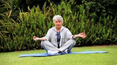 Femme aux cheveux gris, faire du yoga dans le jardin — Vidéo