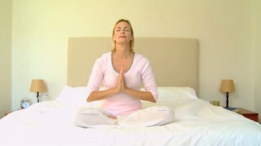 Blonde woman alone on bed doing yoga — Stock Video
