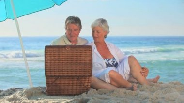 Mature couple picnicking on a beach — Stock Video