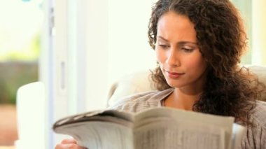 Young woman reading a newspaper — Stock Video